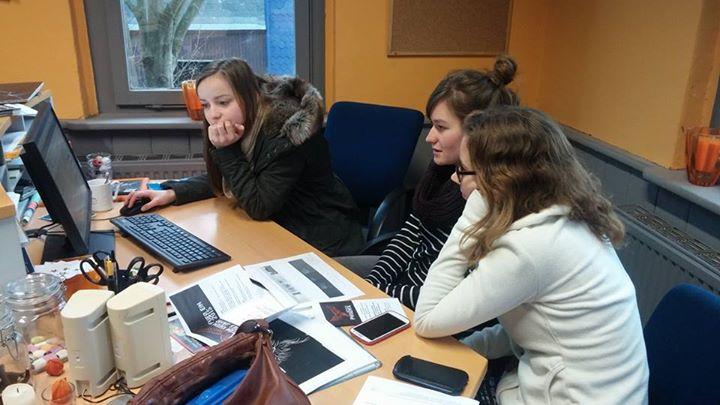 Drei Jugendliche sitzen konzentriert vor einem Bildschirm und arbeiten